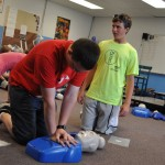 Kids performing CPR on dummy at Algoma Christian